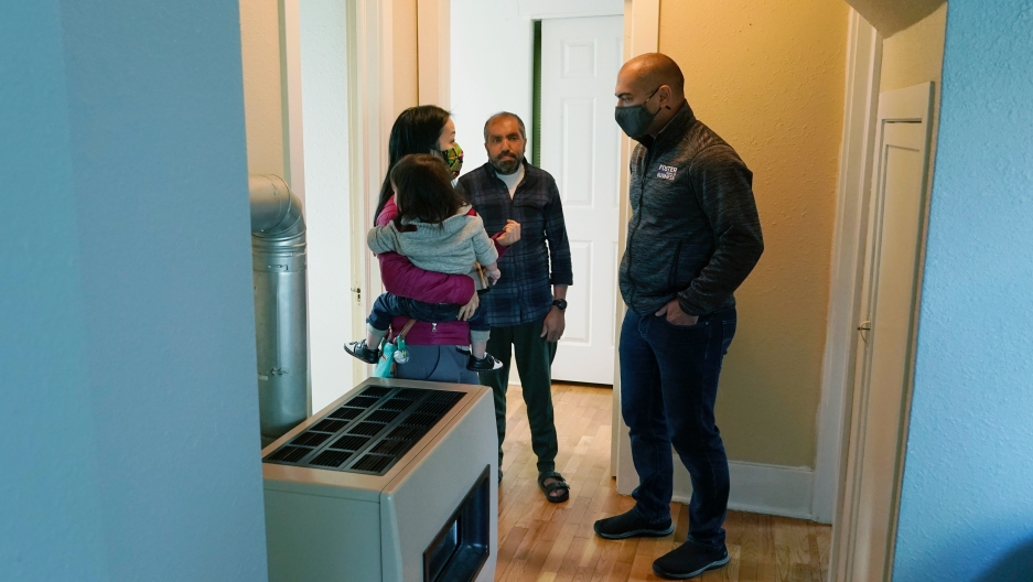 Thuy Do, left, and her husband, Jesse Robbins, right, talk with Abdul, center, Sept. 20, 2021,