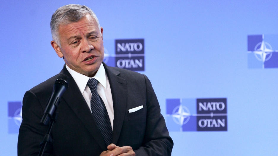 Jordan's King Abdullah II is shown speaking behind a microphone and wearing a dark suit.