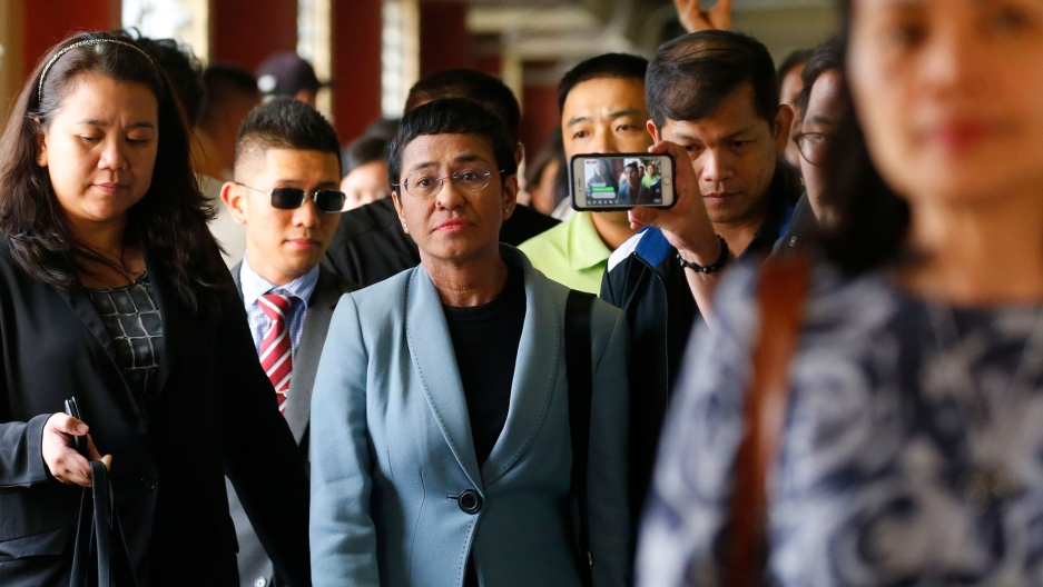 Maria Ressa, center, the award-winning head of a Philippine online news site Rappler, is escorted into the court room to post bail at a Regional Trial Court following an overnight arrest by National Bureau of Investigation agents on a libel case Thursday,