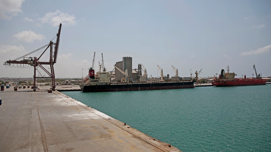 A cargo ship and oil tanker ship sit idle while docked at the port of Hodeida, Yemen