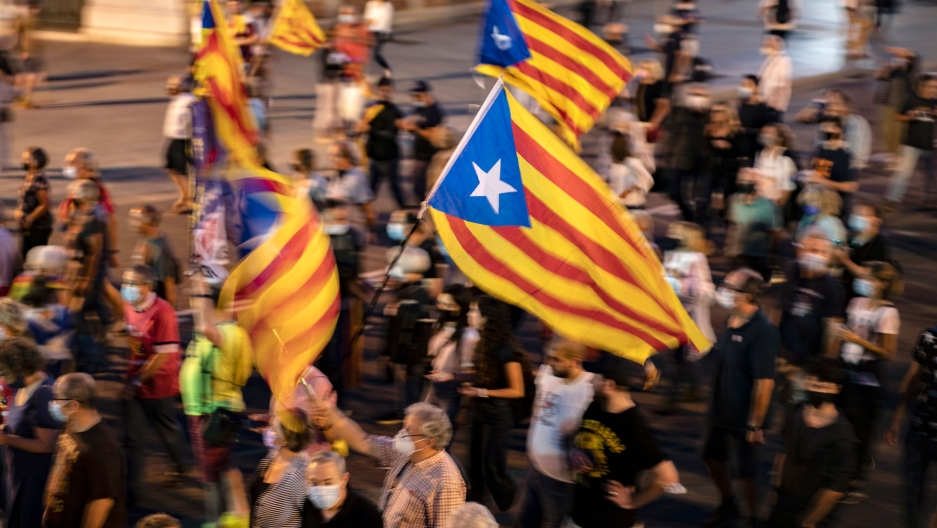 People hold a Catalonian independence flag, as they march during a demonstration to mark the fourth anniversary of a failed independence referendum, in Barcelona, Spain, late Friday, Oct. 1, 2021.