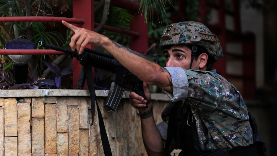 A Lebanese special forces soldier take his position, as he points to his comrades to a position of a shiite group sniper who was sniping at the Christian neighborhood of Ain el-Remaneh, in Beirut, Lebanon, Thursday, Oct. 14, 2021.