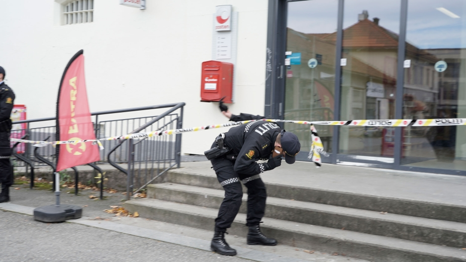 A police officer is shown bending down to walk under yellow caution tape outside of a set of glass doors.