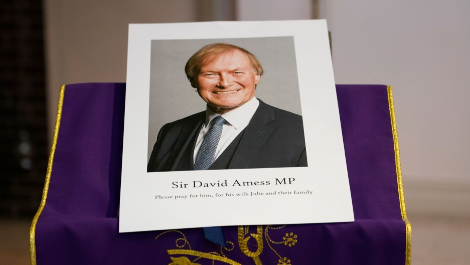 An image of murdered British Conservative lawmaker David Amess is displayed near the altar in St. Peters Catholic Church before a vigil in Leigh-on-Sea, Essex, England, Friday, Oct. 15, 2021.