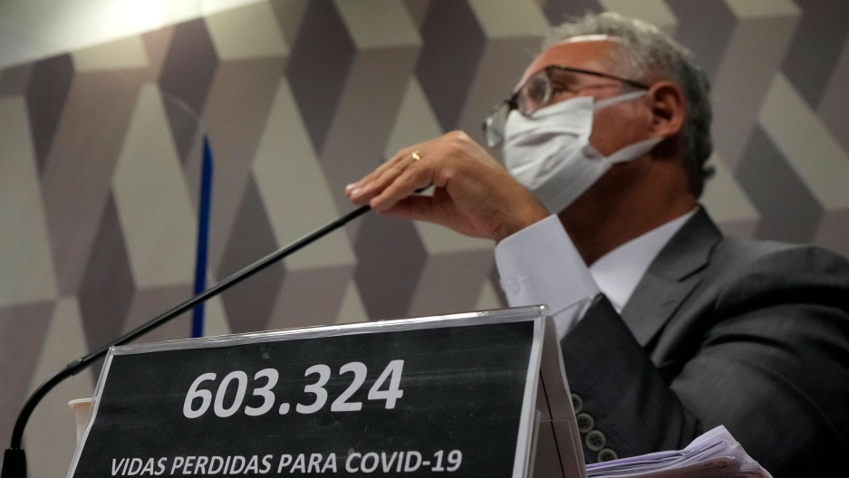 """A plaque reads in Portuguese """"603,324 lives lost to COVID-19"""" in front of Senator Renan Calheiros during the session by a Senate committee investigating the handling of the pandemic by the administration of President Jair Bolsonaro."""