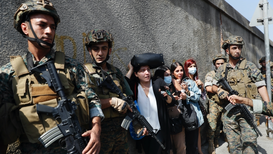 Lebanese teachers react to the sounds from nearby armed clashes as they flee their school under the protection of Lebanese soldiers after a clash erupted along a former 1975-90 civil war front line between Muslim Shiite and Christian areas at Ain el-Ruman