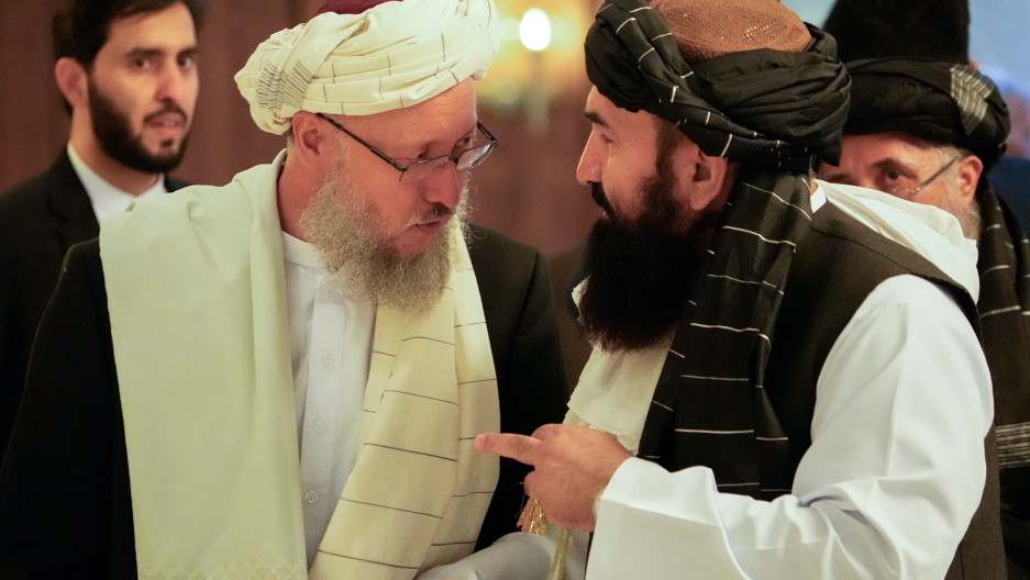 Abdul Salam Hanafi, a deputy prime minister in the Taliban's interim government, left, speaks with acting Foreign Minister of Afghanistan, Taliban official Amir Khan Muttaqi during talks involving Afghan representatives in Moscow, Russia