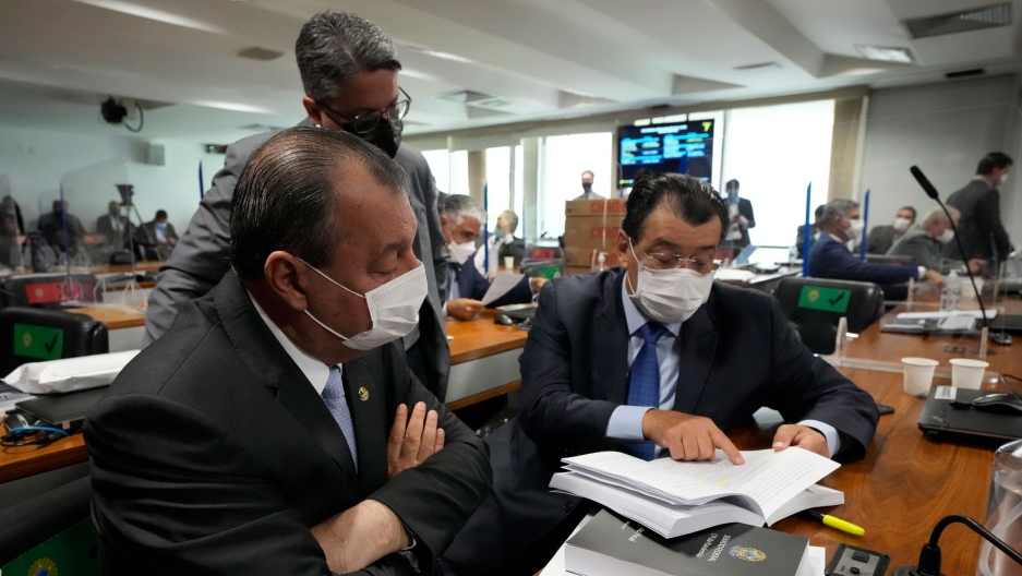 Senators Omar Aziz, sitting left, and Eduardo Braga, right, read a part of a report by a Senate commission that investigated the government's management of the COVID-19 pandemic at the Federal Senate in Brasilia, Brazil, Wednesday, Oct. 20, 2021.