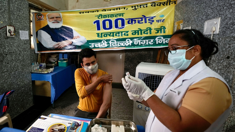 A health worker inoculates a man next to a banner thanking Prime Minister Narendra Modi for 1 billion doses of COVID-19 vaccine at a government hospital in New Delhi, India