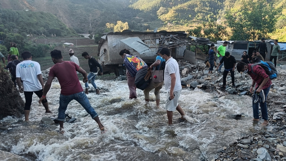 People wade past a flooded area in Dipayal Silgadhi, Nepal.