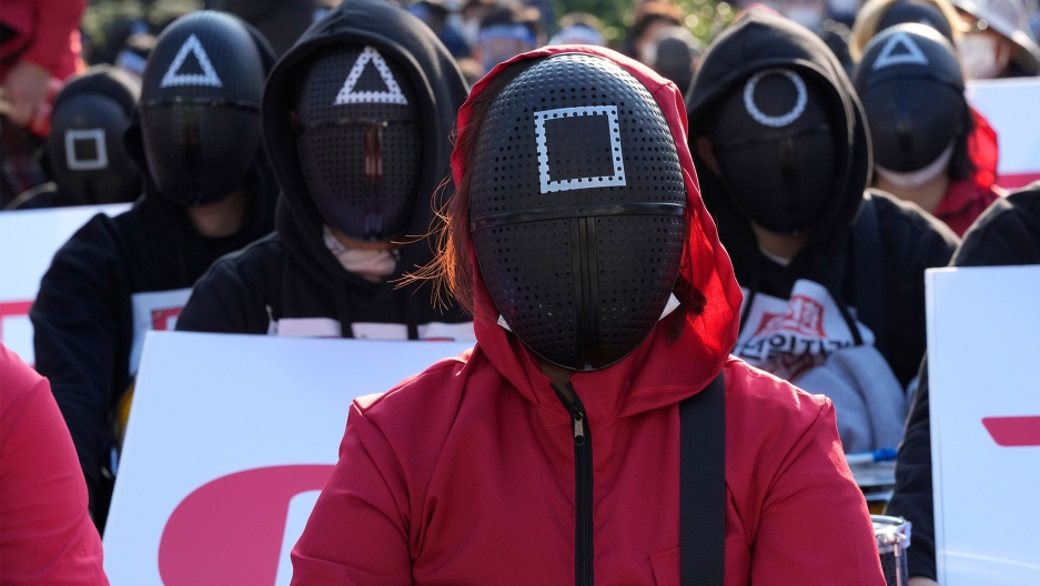 """Members of the South Korean Confederation of Trade Unions wearing masks and costumes inspired by the Netflix original Korean series """"Squid Game"""" attend a rally demanding job security in Seoul, South Korea"""