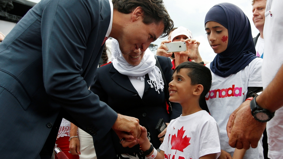 Canada's Prime Minister Justin Trudeau shakes hands with a Syrian refugee during Canada Day celebrations on Parliament Hill in Ottawa, Ontario, Canada, July 1, 2016.