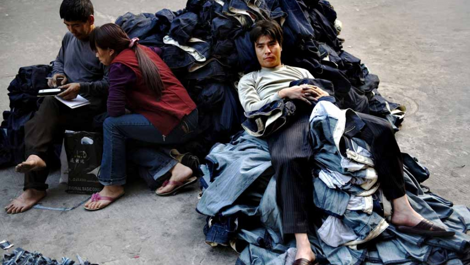 72c377008d5 A worker sits on a pile of jeans in a garment factory in Guangzhou