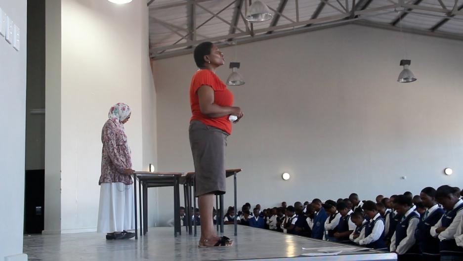Mrs. Booi, a Xhosa teacher at COSAT, leads the school in prayer.