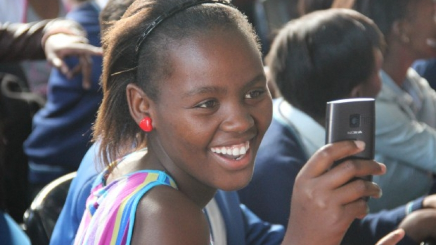 Bridgit, a junior at COSAT, and some of her classmates read books on their cell phones.
