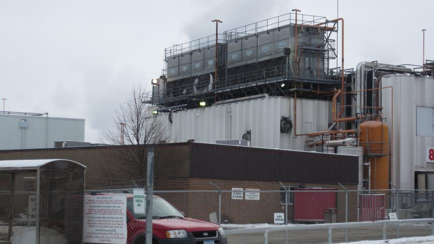 Photo of an industrial agriculture processing plant in the state of Iowa. Complex includes HVAC systems on the roof of a corrugated steel building, external pipes and a singlestory brick building.