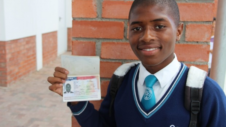 Sive, an eleventh-grader, holds up his US travel visa.