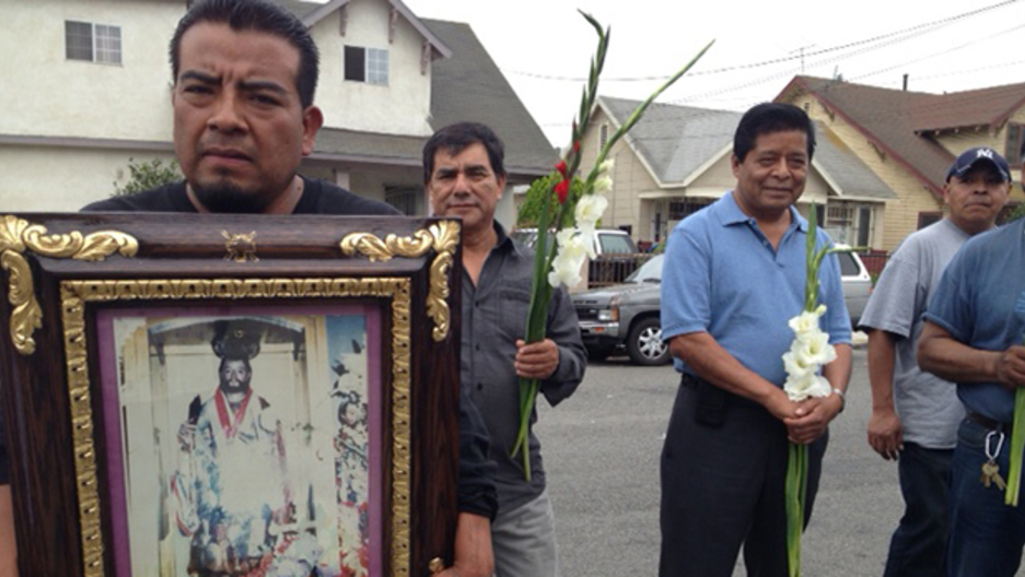 Immigrant holding up large portrait of relative
