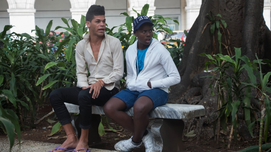 Two Cuban men sit in Havana's Central Park, waiting for customers.