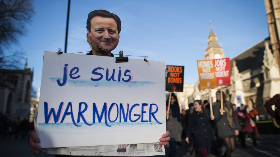 An anti-nuclear protester wearing a mask depicting British Prime Minister David Cameron holds a sign that reads 'I am warmonger' during a protest in central London on January 24, 2015, calling for the British government to abolish the Trident nuclear miss