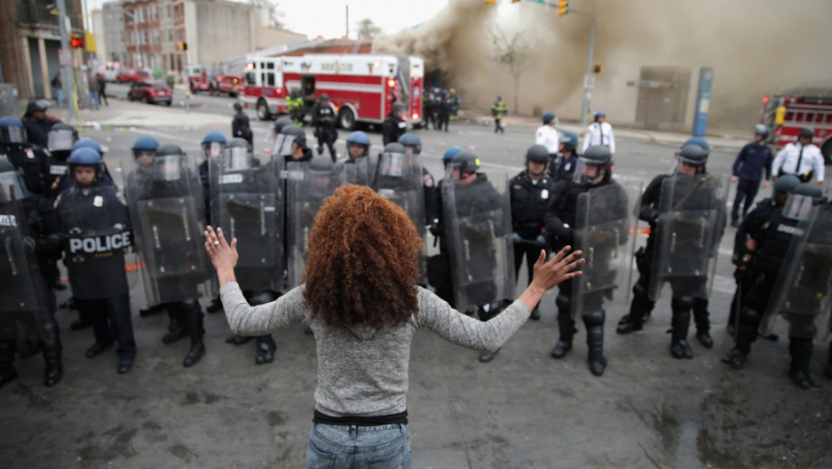 A female protester stands in front of riot police in Baltimore.