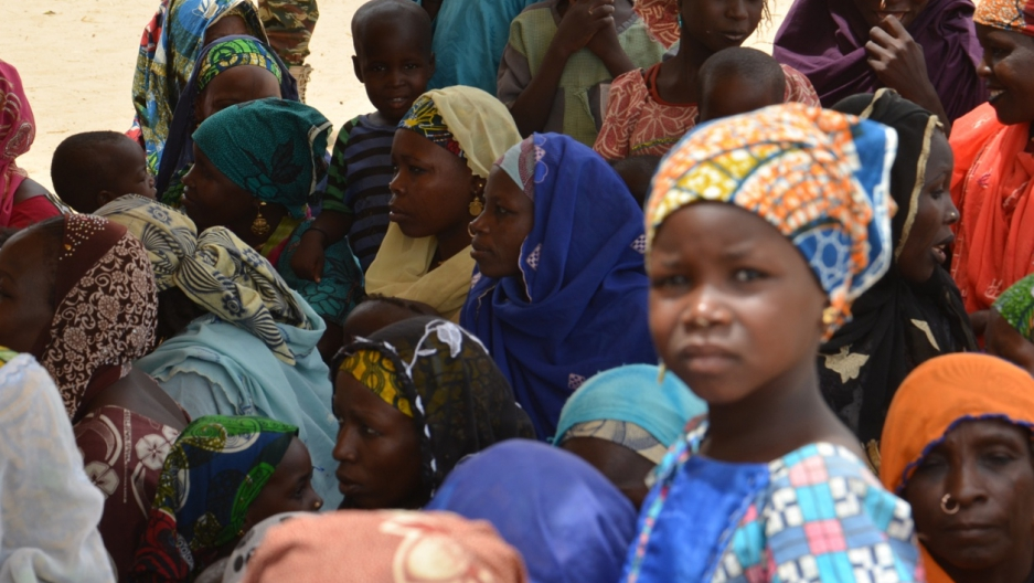 A picture taken on April 3, 2014 in Maine-Soroa, eastern Niger, shows Nigerian people gathered at a camp for refugees who fled the fighting between the Nigerian army and Boko Haram.