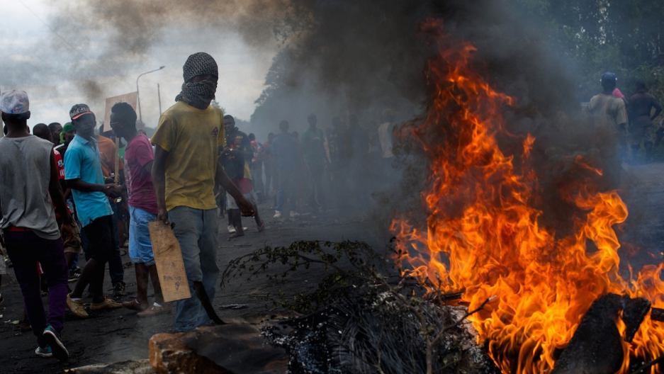 Protesters stand at a burning barricade in the Musaga neighborhood of Bujumbura, Burundi, on May 5, 2015.