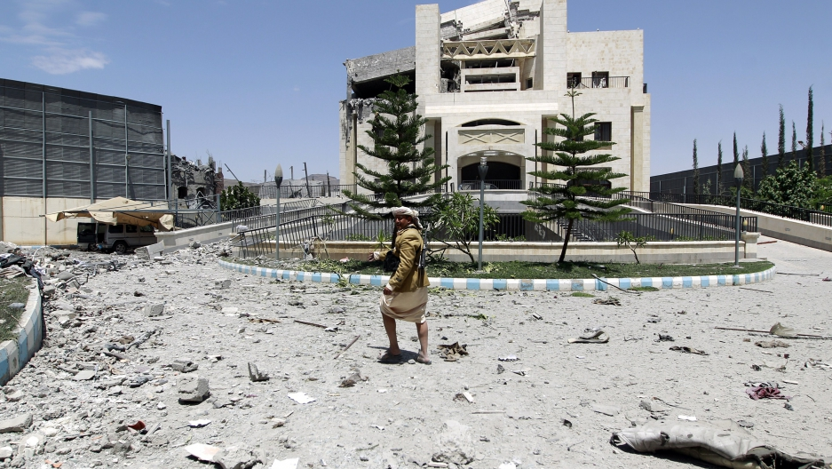 A gunman loyal to former Yemeni President Ali Abdullah Saleh stands amid the wreckage of Saleh's residence following airstrikes on May 10, 2015 in Sanaa.