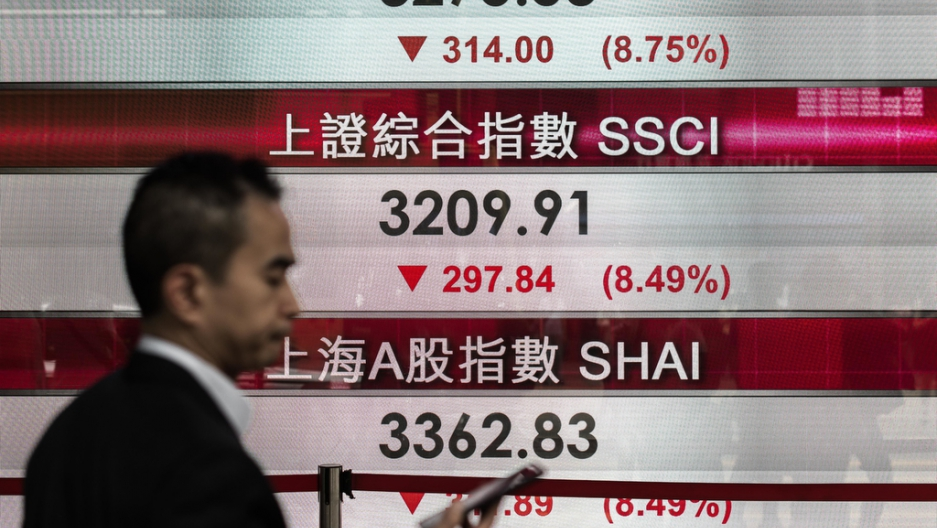 A man checks his cell phone in front of an electronic board displaying stock market information in Hong Kong on Aug. 24, 2015.