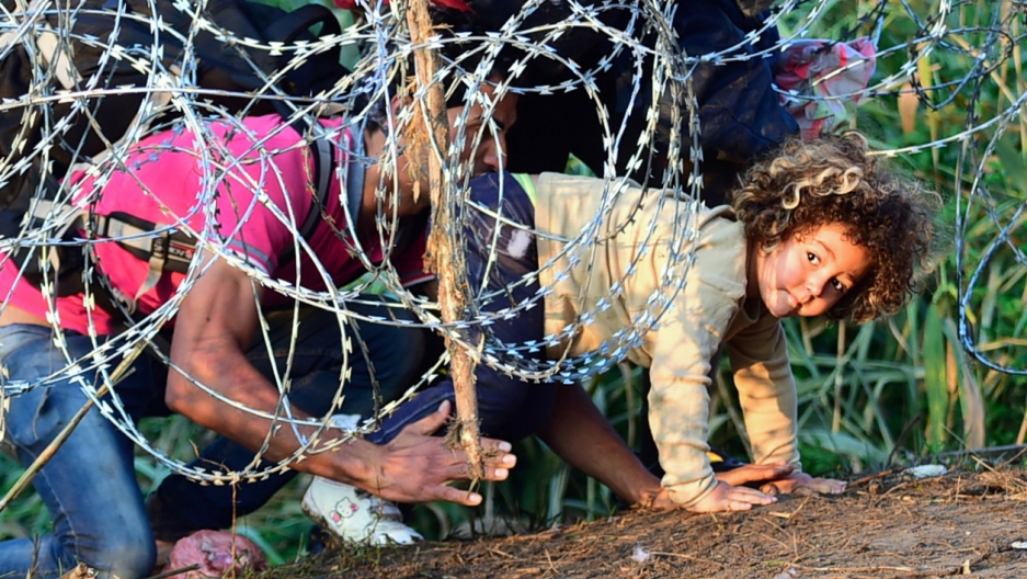 Migrants go under Hungary border fence