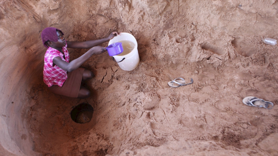 A woman fetches drinking water from a well along a dry Chemumvuri river near Gokwe, Zimbabwe.