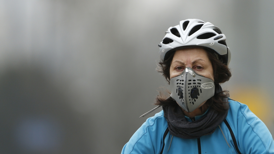 A cyclist wears a mask with an air filter as she cycles through Hyde Park in London on April 3, 2014.