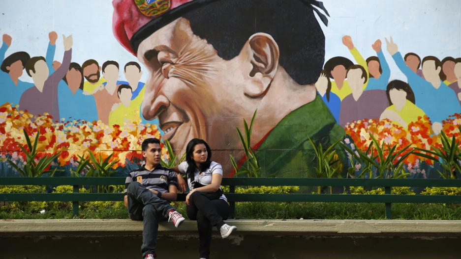 A couple sits in a park next to a mural of late Venezuela's president Hugo Chavez in Caracas on March 9, 2014.