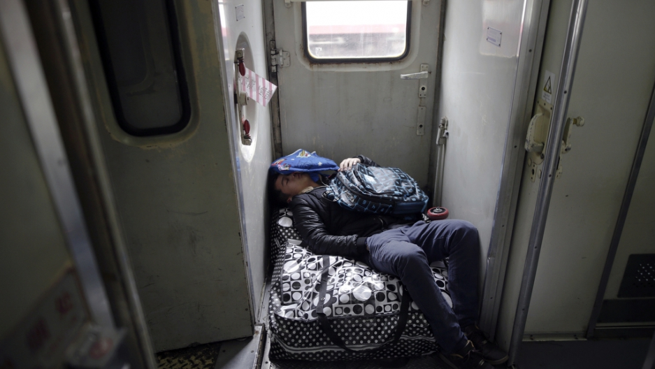 A passenger sleeps on his baggage inside a train from Shanghai to Shijiazhuang at the station in Suzhou, China, on Jan. 27, 2016, after migration for the annual Chinese Lunar New Year and Spring Festival began.