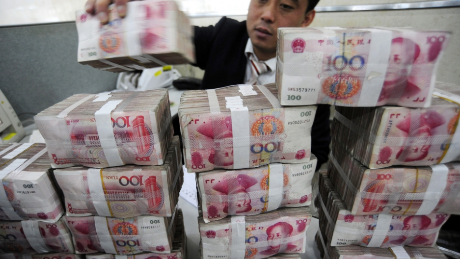 An employee counts renminbi banknotes at a Bank of China branch in Hefei, Anhui province, on Nov. 17, 2009.