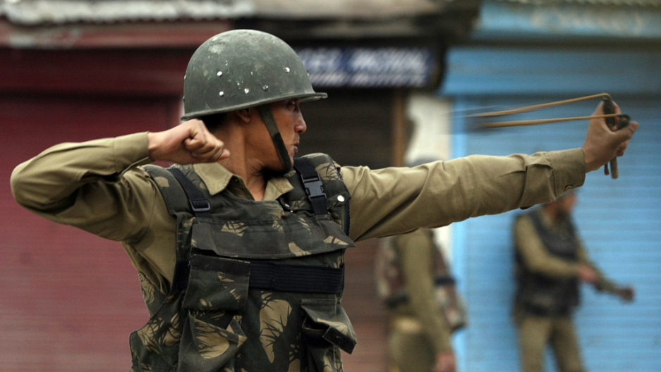 An Indian policeman uses a slingshot to throw stones at Kashmiri protesters during an anti-election protest in Srinagar on May 8, 2009.