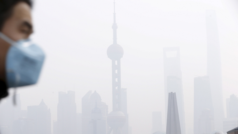 A man wearing a face mask walks across a bridge in front of Shanghai's financial district of Pudong amid heavy smog on Dec. 15, 2015.
