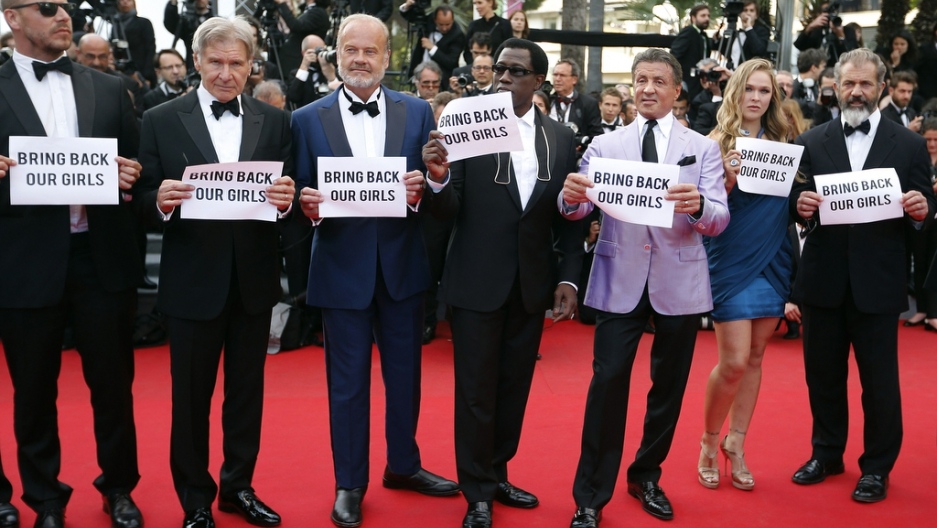 Actors Sylvester Stallone (3rdR) and cast members of the film 'The Expendables 3' hold placards which read 'Bring back our girls' as they pose on the red carpet during the 67th Cannes Film Festival in Cannes on May 18, 2014.