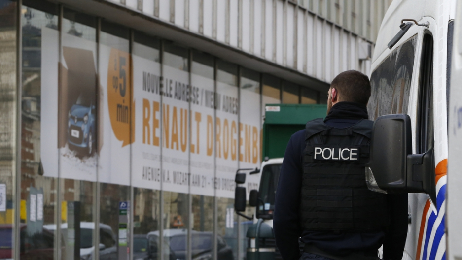 A police officer stands in front of a car dearlership during an operation after fugitive Mohamed Abrini was arrested in Anderlecht, Brussels, on April 8, 2016.