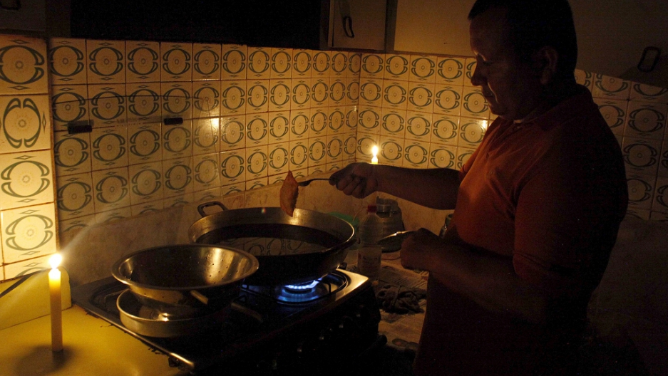 A man cooks near lit candles at his home during a power cut in San Cristobal, in the state of Tachira, Venezuela, on April 25, 2016.