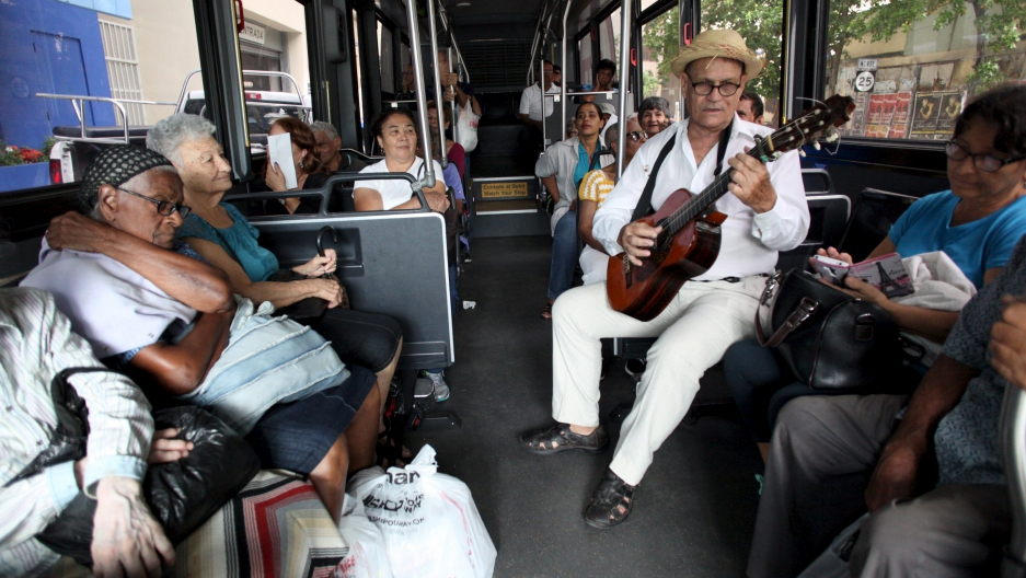 Jorge Luis Jimenez plays the guitar for passengers on a public bus in San Juan, Puerto Rico, on Dec. 2, 2015