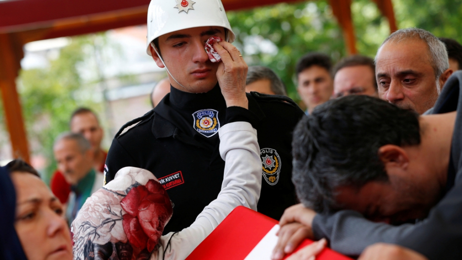 A woman wipes the tears of an honour guard as he stands next to the coffin of police officer Kadir Cihan Karagozlu who was killed in Tuesday's car bomb attack on a police bus, at Fatih mosque in Istanbul, Turkey, June 8, 2016.