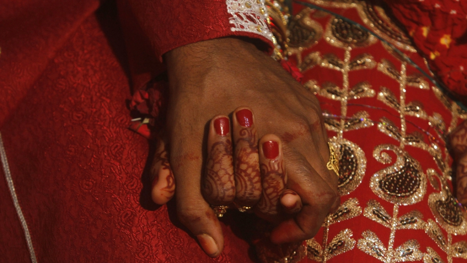 A bride and groom hold hands as they sit together during a mass marriage ceremony held in Karachi on Nov. 30, 2013.
