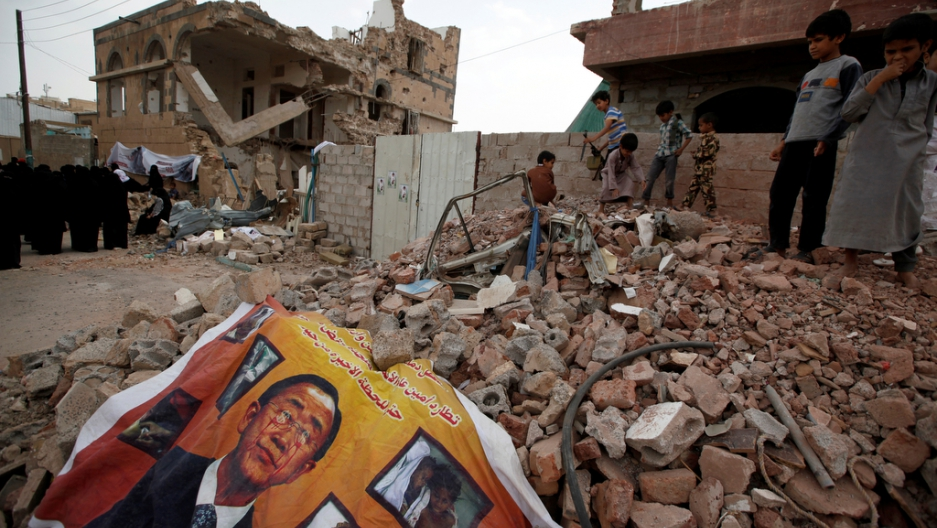 A defaced poster of the U.N. Secretary-General Ban Ki-moon is seen on the rubble of a house during a vigil marking one year since a Saudi-led air strike on a residential area in Sanaa, Yemen June 21, 2016.