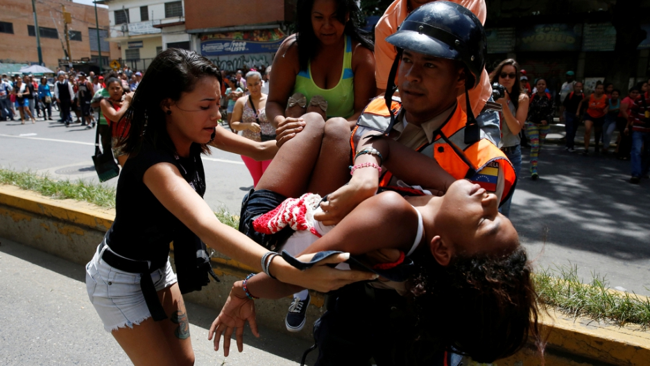 A police officer carries a woman who fainted while gathering to try to buy pasta outside a supermarket in Caracas.