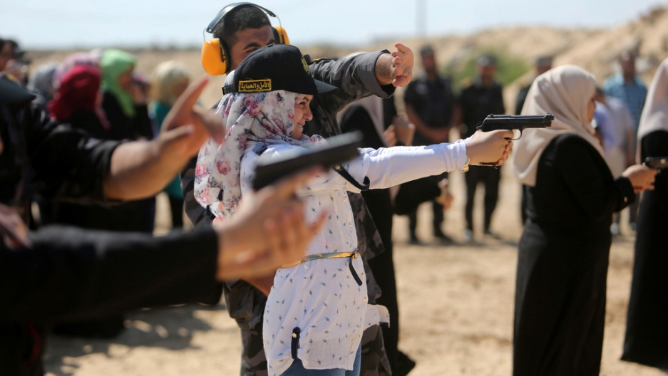 A Palestinian girl aims a pistol as she prepares to fire at a target during a training session for the families of Hamas officials, organized by Hamas-run Security and Protection Service, in Khan Younis in the southern Gaza Strip July 24, 2016.