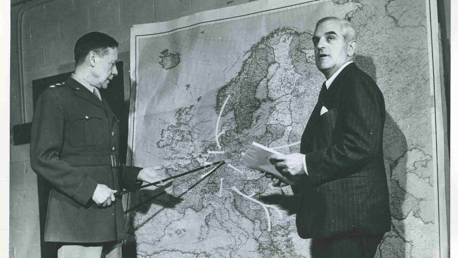 Two men point and look at a map, in black and white