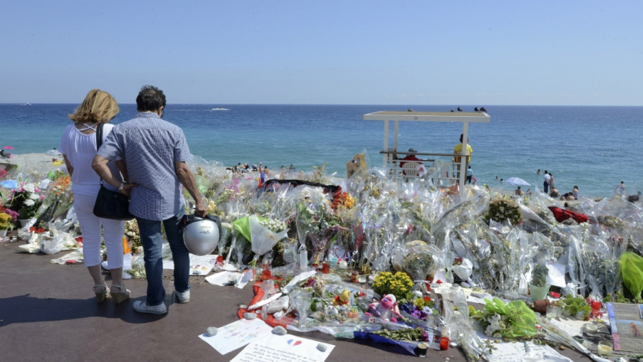 People stop near flowers left in tribute at a makeshift memorial to the victims of the Bastille Day truck attack along the Promenade des Anglais in Nice, France, July 21, 2016.