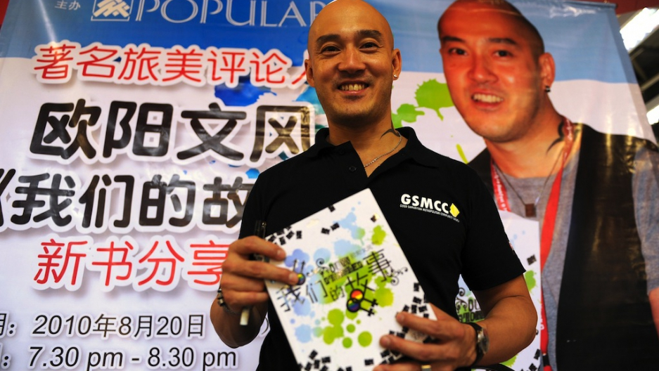 Malaysian's only openly homosexual pastor, Reverend Ouyang Wen Feng, poses  with his book in Kuala Lumpur, Malaysia, on Aug. 21, 2010.