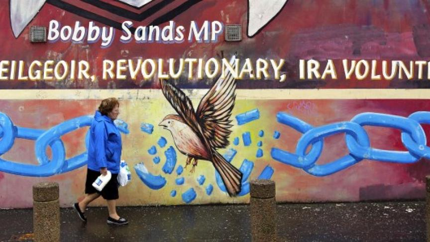 """A woman carries a carton of milk past a Republican mural of """"Gaeilgeoir"""" (Irish speaker) Bobby Sands outside the Sinn Fein offices on the Falls road in West Belfast (Reuters/Cathal McNaughton)"""